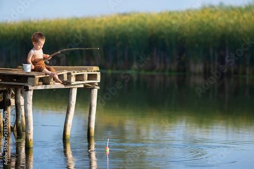 Obraz na plátně little boy fishing on the lake