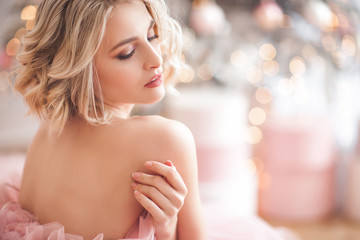 Beautiful young blond woman closeup. Lady on christmas background. Portrait of pretty female indoors.