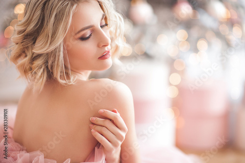 Fototapeta Beautiful young blond woman closeup. Lady on christmas background. Portrait of pretty female indoors. obraz
