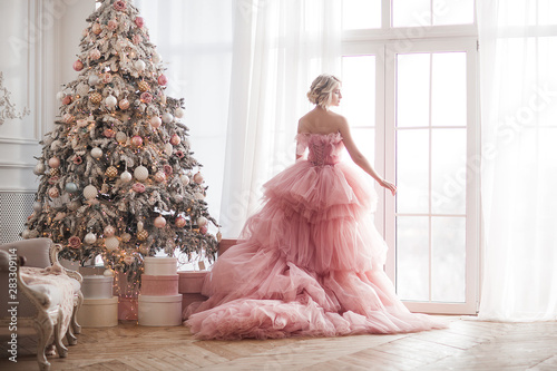 Young beautiful blond woman on christmas background full height Fototapet