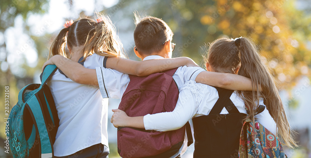 Fototapety, obrazy: school friends a boy and two girls with school backpacks on their backs walk after class