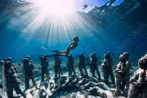Photo  Woman freediver with fins dive near underwater statues