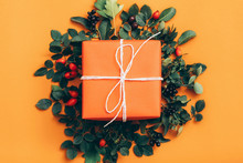 Floral Decoration. Handmade Gift Box With Rose Hip Berries And Green Leaves On Orange Background.
