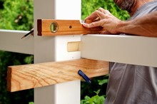 Carpentry Joints. Wood Post, Rabbet Joint. Mounting The Carport. Carpenter Using A Spirit Level To Connect A Spruce Wooden Beam For Carport Outdoor Construction. Woodworking And Carpentry Concept.