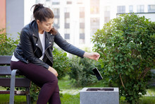 Young Woman Throwing Smartphone In Litter Bin Outdoors