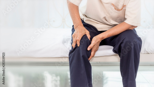 Cuadros en Lienzo  Health problem concept; old woman suffering from knee pain at home