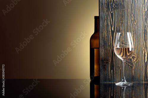 Fotografie, Obraz  Bottle and glass of white wine on a black table.