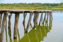 Empty Old Footbridge On The Lake. The Bridge Is Handicraft. Low Water Level In The Lake In Ukraine.