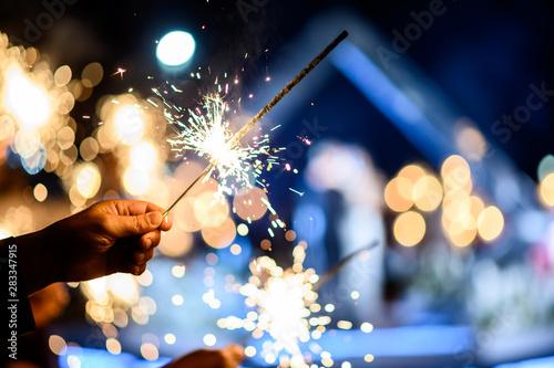 Obraz Man hand holding a burning sparkler. Bengal fire - fototapety do salonu