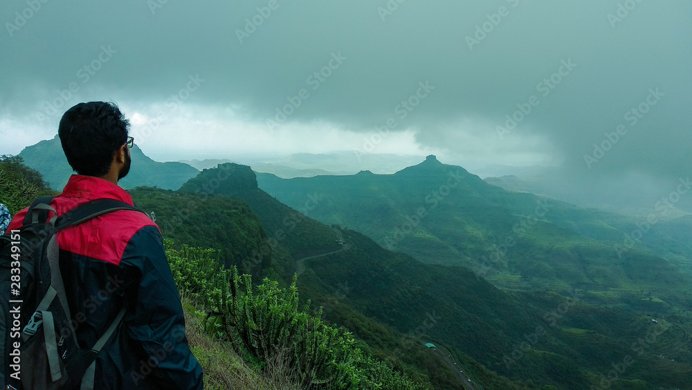 Fototapety, obrazy: A person looking at a mountain peak