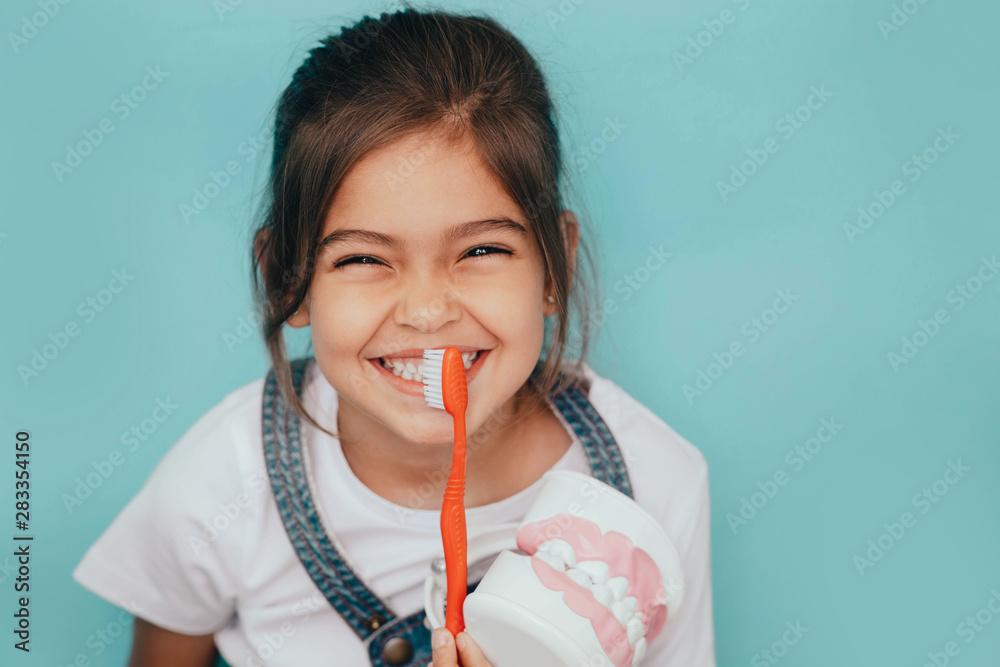 Fototapeta Yes, my teeth is clean. Cute mixed raced girl brushing teeth at blue background.