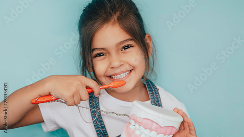 smiling mixed raced girl brushing teeth at blue background. Wallpaper Mural