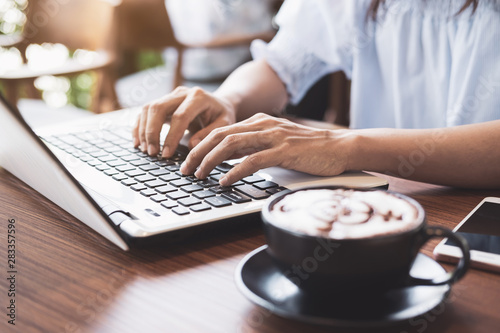 Young woman using smart phone and laptop with cup of coffee in cafe - 283357596