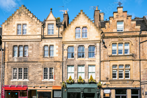 Valokuva  Historic stone buildings with colourful shops at the ground level in Edinburgh old town on a clear winter day