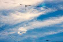 Blue Sky With White Feathery Clouds And Intersecting Wires