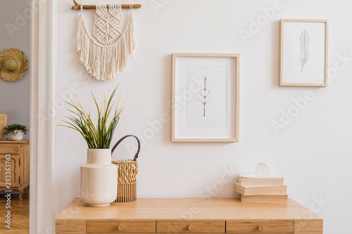 Photo Stylish and modern boho interior of living room with mock up photo frames, flowers in vase, wooden desk, beige macrame and elegant accessories