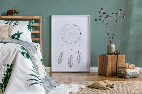 Fotografía  Stylish and modern composition of bedroom interior with wooden bed, mock up poster frame, cube, vase with flowers, books and elegant accessories