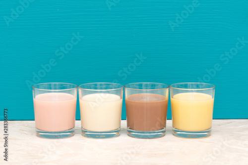 Flavoured milkshakes and fresh creamy milk in glass tumblers