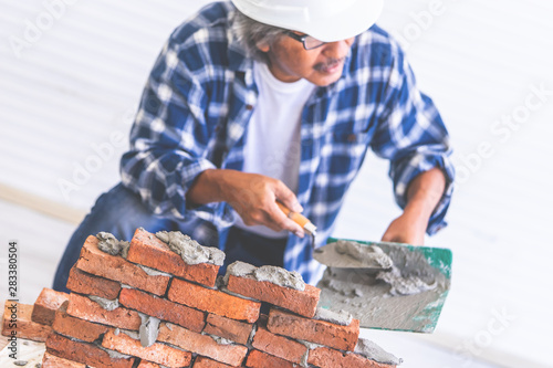 Old Builder craftman is leveling brick wall Tablou Canvas