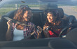 Two beautiful young women putting on seatbelt while smiling