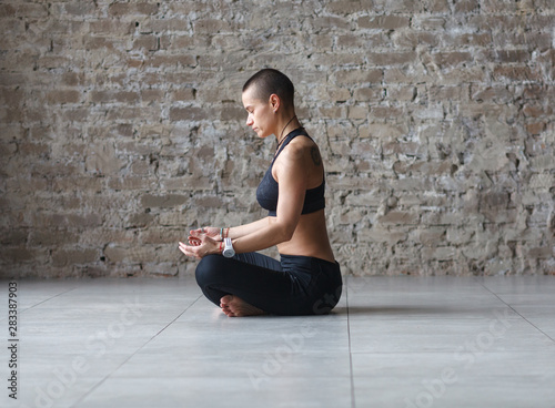 short hair woman in lotus pose in loft interior, side view