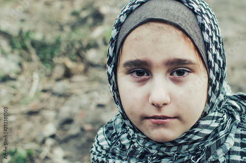 Fotografía a refugee child in the war, a Muslim girl with a dirty face on the ruins, the concept of peace and war, the child is crying and waiting for help