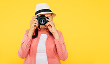 Vacation. Tourism And Travels. Happy Emotional And Modern Senior Woman In Hat With Photo Camera In Hands Is Posing On Yellow Background.
