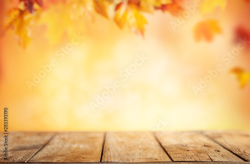 Cadres-photo bureau Automne Wooden table and blurred Autumn background. Autumn concept with red-yellow leaves background.