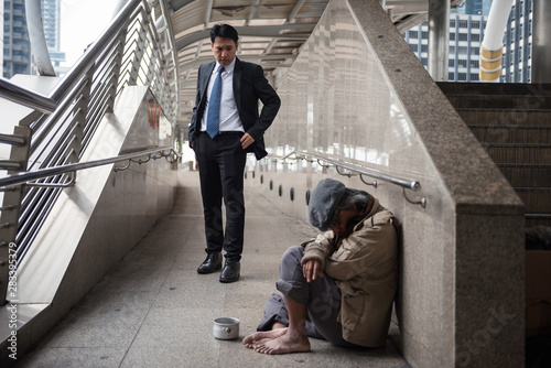 Mercy Businessman look at Homeless in city Canvas Print