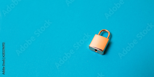 Fotografía  Locked golden padlock on the blue background.