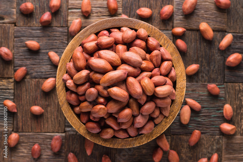 Poster Pays d Europe peanut indian peeled in wooden bowl, top view.