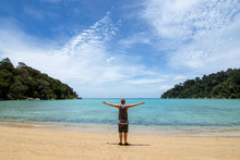 Man With Arms Out Wide On A Empty Idlic Paradise Beach In An Empty Bay With Tree Lined Headland.