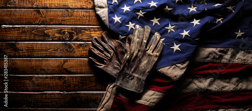 Old and worn work gloves on large American flag - Labor day background - 283415387