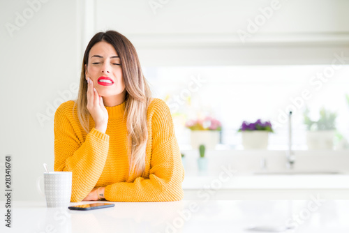 Fotografia Young beautiful woman drinking a cup of coffee at home touching mouth with hand with painful expression because of toothache or dental illness on teeth