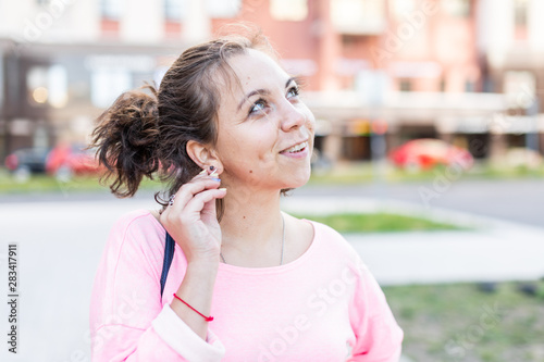 Photo Young stylish Caucasian hipster woman thoughtfully pulls the earring on summer street