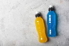 Isotonic Energy Drink. Bottles With Blue And Yellow Transparent Liquid, Sport Beverage On A Gray Concrete Background