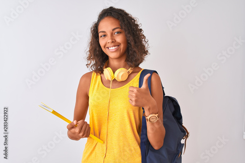 Obraz Brazilian student woman wearing backpack holding notebook over isolated white background happy with big smile doing ok sign, thumb up with fingers, excellent sign - fototapety do salonu