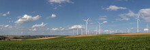 Panoramic View Of Wind Turbines On The Fields Under A Blue Sky With Some Clouds
