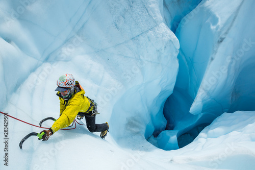 Fototapeta Ice climber expertly ascending out of a massive mouin in the Matanuska Glacier