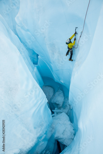 Following out of a large moulin after his friend lead a steep ice climb.
