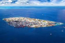 Aerial View On Male The Capital City Of Maldives. Overcrowded Island In The Indian Ocean  Blue Ocean Sea Background