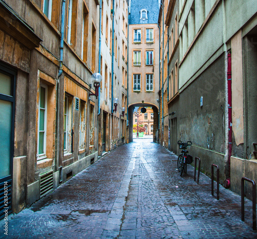 Colorful empty narrow cobblestone alley through old buildings to archway