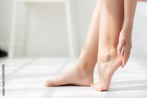 Closeup beautiful young asian woman applying cream and lotion onto foot dry on bed, beauty asia girl moisturizer and treatment cosmetic onto toes and heel, skincare cosmetic and healthy concept Obraz na płótnie