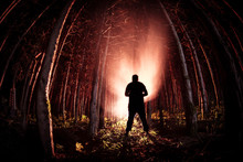 Strange Light In A Dark Forest At Night. Silhouette Of Person Standing In The Dark Forest With Light. Dark Night In Forest At Fog Time. Surreal Night Forest Scene.