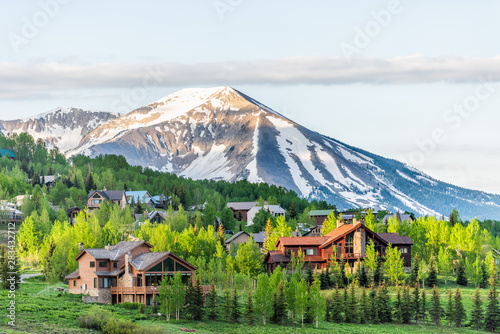 Mount Crested Butte, Colorado village in summer with colorful sunrise by wooden lodging houses on hills with green trees