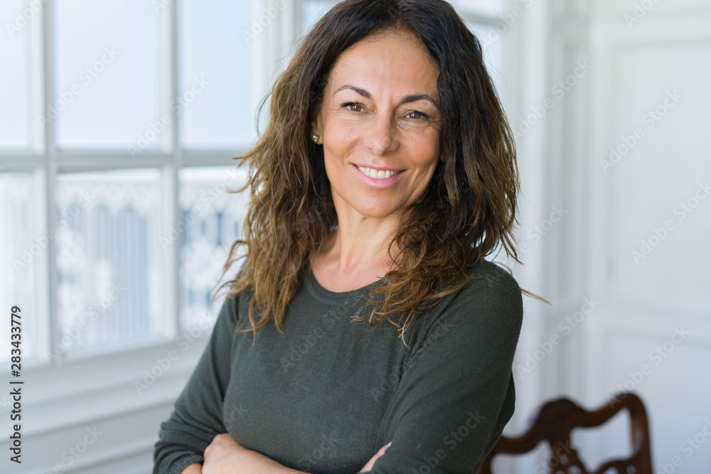 Fototapeta Beautiful middle age woman at home smiling cheerful with arms crossed