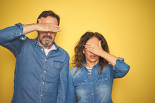 Beautiful Middle Age Couple Together Standing Over Isolated Yellow Background Covering Eyes With Hand, Looking Serious And Sad. Sightless, Hiding And Rejection Concept