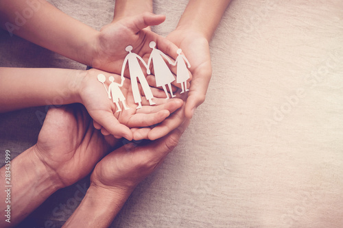 Obraz hands holding paper family cutout, family home, adoption foster care, homeless charity , family mental health, Autism support , domestic violence, trust, social distancing, isolation concept - fototapety do salonu