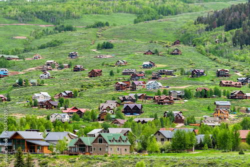Poster Olive Mount Crested Butte village town in summer with colorful grass and many wooden lodging houses on hills with green lush color