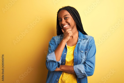 Photo sur Toile Les Textures Young african american woman wearing denim shirt standing over isolated yellow background looking confident at the camera smiling with crossed arms and hand raised on chin. Thinking positive.